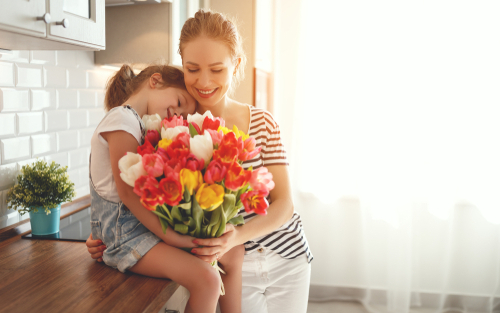 Image of a mum and child holding bouquet of flowers for Mother's Day